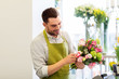Leinwandbild Motiv people, business, sale and floristry concept - happy smiling florist man making bunch at flower shop