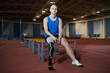 Young paralympic runner with artificial right leg sitting on bench after marathon on stadium