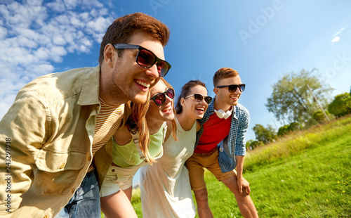 leisure, people and friendship concept - happy teenage friends laughing outdoors in summer