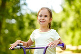 childhood, leisure and people concept - happy little girl with bicycle in summer - 243298356
