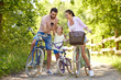family, leisure and technology concept - happy mother, father and little daughter with smartphone and bicycles in summer park - 243298747