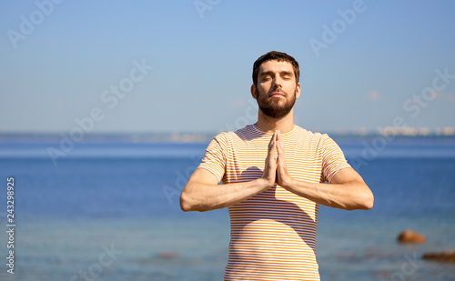 Leinwanddruck Bild meditation, spirituality and mindfulness concept - man meditating outdoors over sea