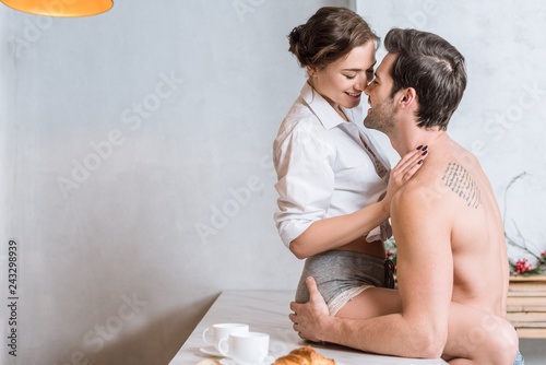 adult couple embracing and smiling at kitchen while woman sitting at tabletop