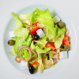 Greek salad with olives, onion, feta cheese, romaine lettuce and tomatoes on a plate. - 243299726