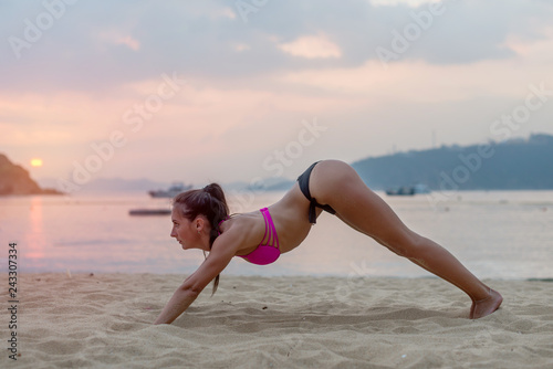 Young woman in swimsuit exercising on beach stretching her legs during sunset at sea. Fitness girl doing exercises on seashore