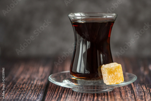 Turkish glass for tea bardak with turkish delight on dark wooden table