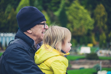 Toddler and grandfather in garden with model houses