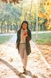 Smiling young asian woman wearing coat walking