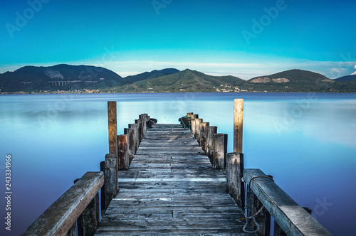Acrylglas Pier Wooden pier or jetty on a blue lake sunset and sky reflection on water. Versilia Tuscany, Italy