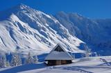 tatrzański zimowy pejzaż z zaśnieżoną chatką w Dolinie Gąsienicowej