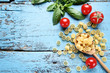 Uncooked pasta with tomatoes and basil leafs on blue wooden table