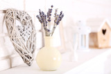 Lavender flowers in vase with decorative heart on white fireplace
