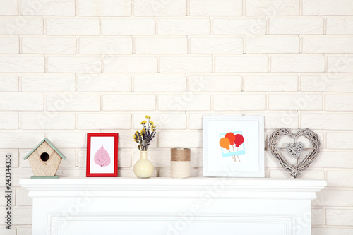 White fireplace with photo frames, nesting box and flowers in vase - 243344336