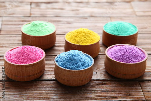 Colorful holi powder in bowls on brown wooden table