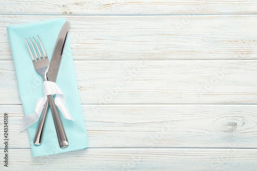 Fork and knife with napkin on wooden table