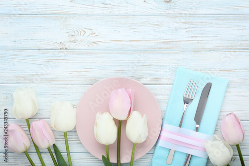 Kitchen cutlery with plate and tulip flowers on wooden table