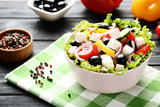Vegetable salad in bowl with napkin and spices on wooden table - 243346993