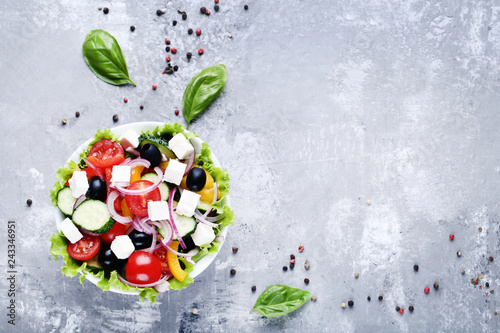 Vegetable salad in bowl with basil leafs on grey background