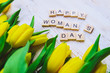 happy woman's day text. tulips overhead on white wooden background