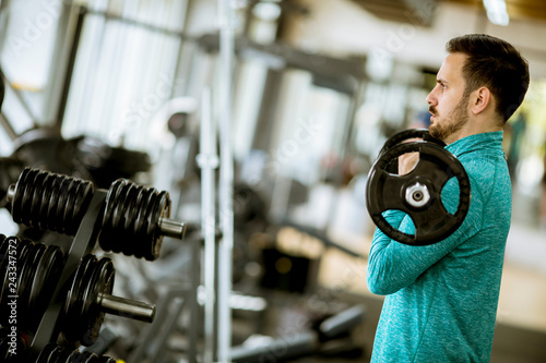 Foto Murales Handsome young man uses dumbbells in gym