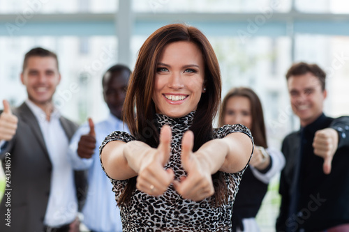 Leinwandbild Motiv business concept - attractive businesswoman with team in office showing thumbs up.