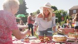 Slow Motion Shot Of Mature Woman Serving On Cake Stall At Busy Summer Garden Fete - 243354134