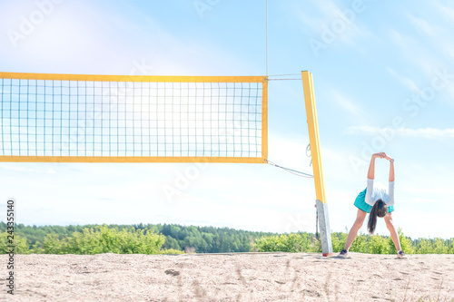 girl athlete warming up on a volleyball court, bend forward and down, hands up