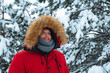 young adult man in red winter coat with hood with fur. snowed fir-tree on background