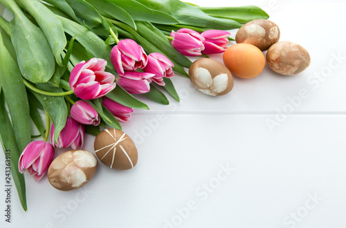 Foto Murales Easter background with bouquet of pink tulips and colorful eggs .