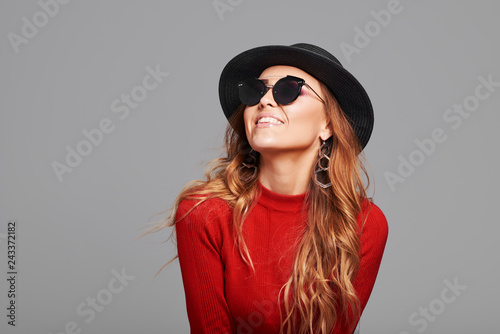 Fashion portrait pretty woman in black rock style hat and sunglasses over grey background. Holiday concept