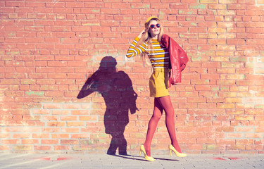 Urban Fashion. Young playful blonde woman walking in the street near Art wall wearing Stylish Sunglasses. Beautiful Girl in Trendy fashionable spring Outfit