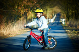 Boy riding his bike on a spring country track.  Road concept for safety and child development - 243376915