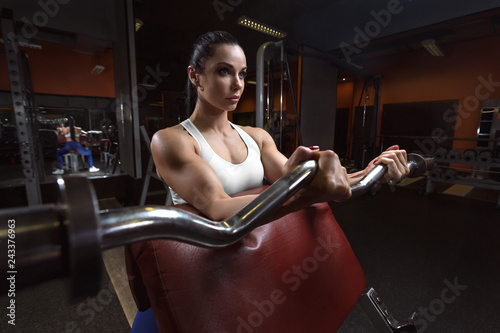 Pretty young woman is doing bicep curls in the training apparatus at the gym