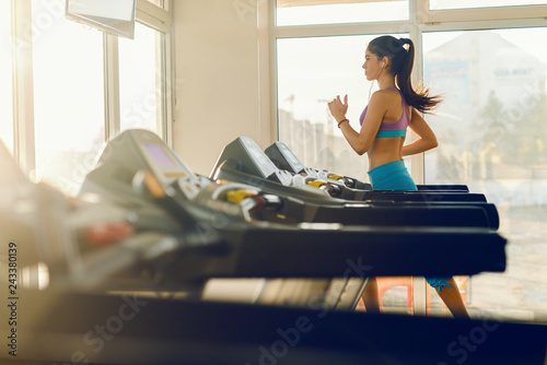 Young Caucasian sporty woman running on treadmill. Gym interior.