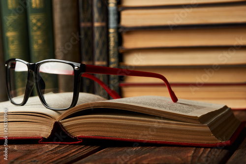 Foto Murales Old books and reading glasses on desk in library room