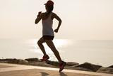 Fitness sportswoman running on sunny coast - 243394367