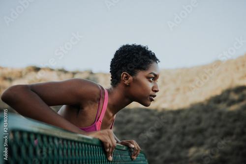 Leinwanddruck Bild Woman stretching against a park bench