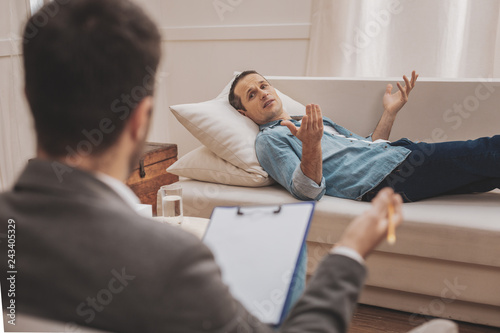Stressed man lying on beige sofa explaining his problems to therapist