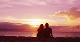 Couple romantic relaxing on beach looking at sunset at honeymoon travel vacation. - 243406326