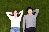 young asian couple lying on the lawn - 243421300