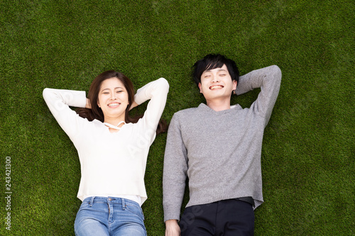 Foto Murales young asian couple lying on the lawn