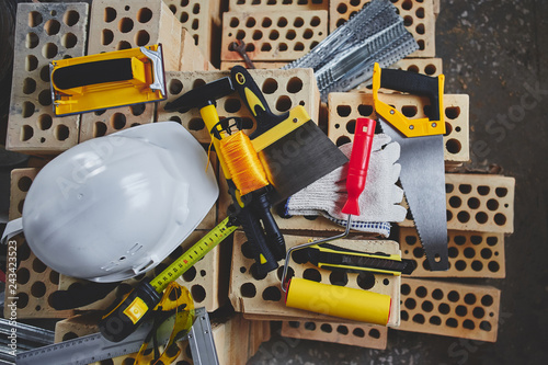 Home repairs. Construction tools, bricks and helmet top view - 243423523