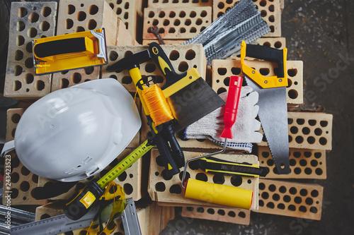 Home repairs. Construction tools, bricks and helmet top view - 243423523