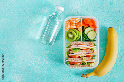 Leinwandbild Motiv School lunch box with sandwich, vegetables, water, and fruits on table. Healthy eating habits concept. Flat lay. Top view