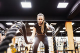 Portrait of a beautiful positive hardy young female fitness model engaged with ropes in the gym. The concept of a strong feminist girl loving sport - 243433951