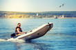 Inflatable white motor boat with driver under bright sun
