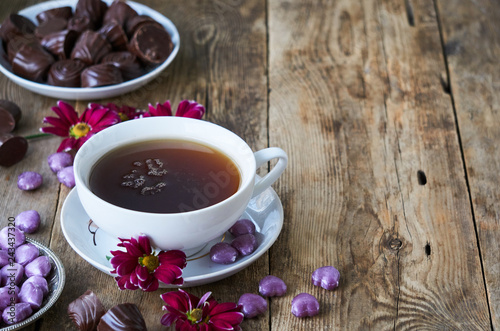 A cup of black tea with candies and flowers on a wooden table