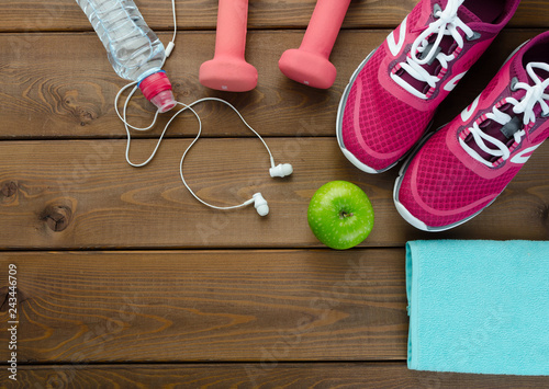 Sneakers dumbbells bottle of water and apple on wooden table