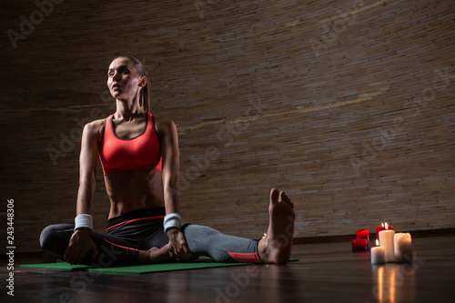 Fit woman doing yoga on the mat while being alone