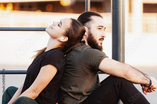 Beautiful multiracial couple of young athletes - a charming girl and a stylish guy are resting after a long grueling joint workout sitting back to back on the surface of a street sports field